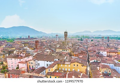 Panoramic view on roofs of medieval Italian town with high bell towers and shabby tile roofs of residential houses, Lucca, Italy