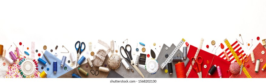Panoramic view on sewing composition with threads, fabrics, scissors, buttons, needles, pins and other sewing accessories on white background. Long banner, top view, copy space, flat lay, mock up