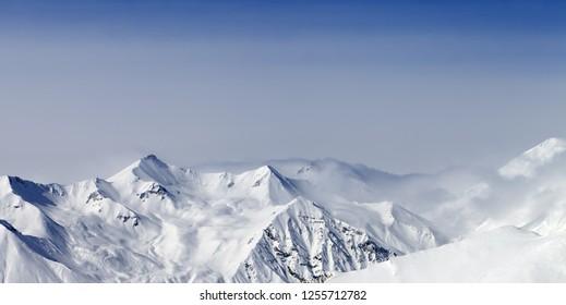 Panoramic view on snowy sunlight mountains in haze. Caucasus Mountains at winter, Georgia, region Gudauri.