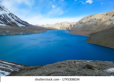 A panoramic view on turquoise colored Tilicho lake in Himalayas, Manang region in Nepal. The world's highest altitude lake (4949m). Snow capped mountains around. Calm surface of the lake. Serenity