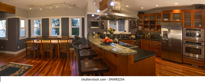 Panoramic view of open plan kitchen and dining area in upscale contemporary home interior, featuring wood floors, granite countertops, stainless steel appliances, view windows and accent lighting