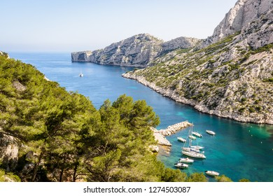 Panoramic view over the calanque de Morgiou on the mediterranean shore near Marseille, France, with sailboats mooring in the turquoise waters and the cap Morgiou in the distance on a sunny spring day.