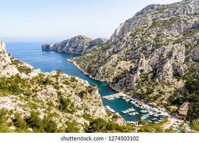 Panoramic view over the calanque de Morgiou on the mediterranean shore near Marseille in the south of France, with its small fishing port and the cap Morgiou in the distance on a sunny spring day.
