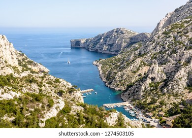 Panoramic view over the calanque de Morgiou on the mediterranean shore near Marseille in the south of France, with its small port and the cap Morgiou in the distance on a sunny spring day.