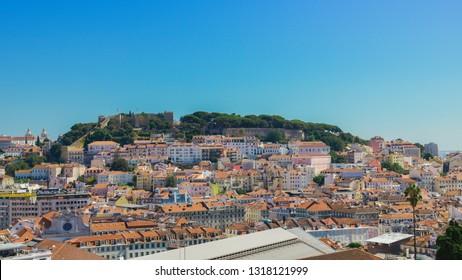 panoramic view over the center of Lisbon from the viewpoint called: Miradouro de Sao Pedro de Alcantara featuring the Baixa neighbourhood and Castelo Sao Jorge