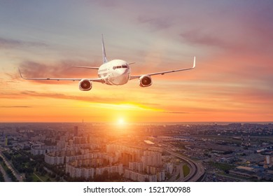 Panoramic view over the evening city during sunset, and a flying passenger plane