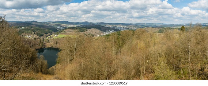 Panoramic view over the hills of the south Eifel landscape near Daun, Germany. The lake to the left is the Gemundener Maar, an old volcanic crater lake.