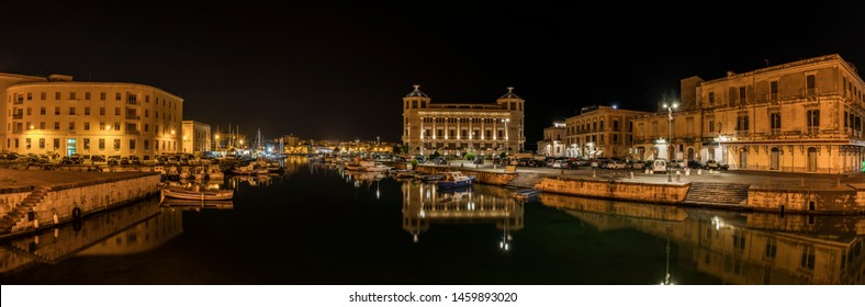 Panoramic view over the island Ortigia and its sea port at night with illumination and reflection in water, city of Syracuse in Sicily, south Italy