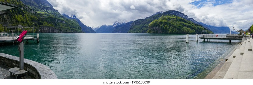 Panoramic view over Lake Lucerne (Switzerland) from the boulevard of Brunnen, with red binoculars and the stone steps of the lake boulevard.