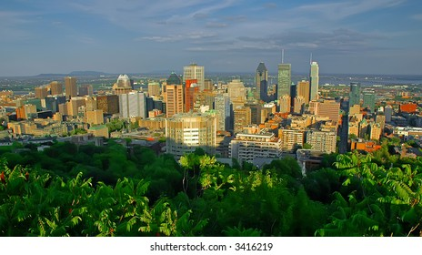 Panoramic view over the skyline of Montreal (Quebec, Canada) at sunset. It is taken from a viewpoint on the Mont Royal. The foreground is dominated by green trees.