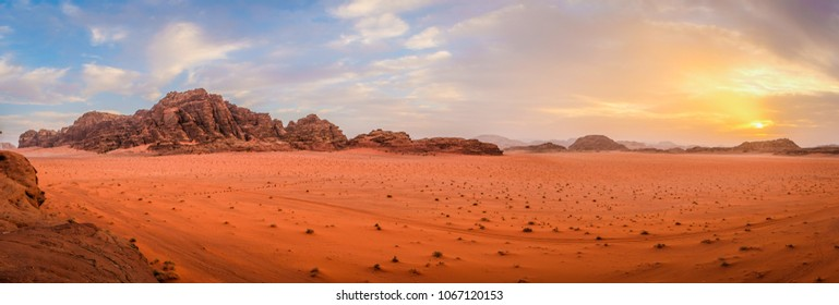 Panoramic view overlooking the red sand desert and Bedouin camp as seen with a cloudy golden sunset in Wadi Rum, Jordan