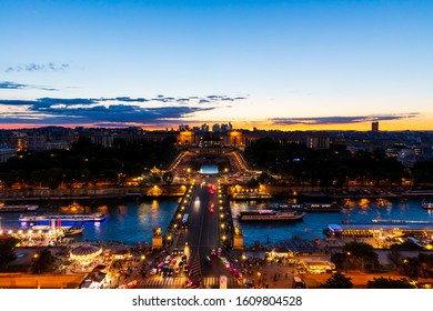Panoramic view of Paris at night seen from the first floor of the Eiffel Tower. Long-exposure shot during sunset showing Pont d'Iéna (Jena Bridge), a bridge spanning the River Seine.