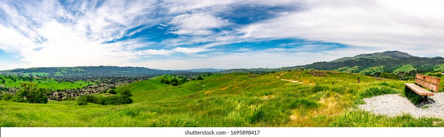 Panoramic view with a park bench overlooking Camino Tassajara on the slope of a hill in Sycamore Valley Preserve Contra Costa County Danville, California.