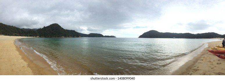 Panoramic view of peaceful bay early in the morning with kayaks prepared for adventure on the right. Anchorage Bay, Able Tasman National Park, New Zealand.