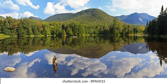 Panoramic view of Phelps Mt, Mt Marcy and Mt. Colden reflected in Marcy Dam Pond in the High Peaks region of the Adirondack Mountains of New York