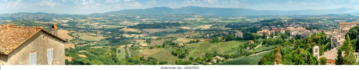 Panoramic view from Piazza Garibaldi in city of Todi, Province of Perugia, Italy. Scenic view of Via Ponti Lunghi and classic Italian landscape. Mountains, meadows and olive trees. Umbria.