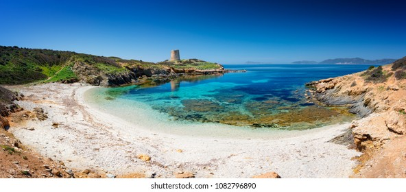 Panoramic view of Piscinni' ( Teulada Sardinia) bay with calm and turquoise sea, and on background the famous coastal tower of Piscinni'.