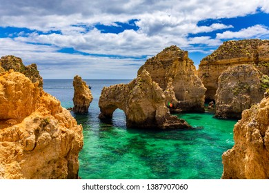 Panoramic view, Ponta da Piedade near Lagos in Algarve, Portugal. Cliff rocks and tourist boat on sea at Ponta da Piedade, Algarve region, Portugal. Ponta da Piedade, Algarve region, Portugal.