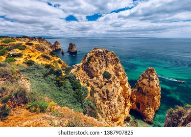 Panoramic view, Ponta da Piedade near Lagos in Algarve, Portugal. Cliff rocks and tourist boat on sea at Ponta da Piedade, Algarve region, Portugal. Ponta da Piedade, Algarve region, Portugal.