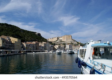 Panoramic view of the port of Bonifacio, with yachts, boats, pier and buildings, overlooked by ancient Bastion de l'Etendard; Bonifacio (Bunifaziu), Corsica, France; 08/09/2014
