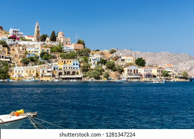 panoramic view of the port of Symi with the nose of a little fishing boat in the foreground