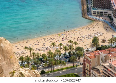 Panoramic view of Postiguet beach  from Santa Barbara Castle in Alicante, Spain. Sunny day at Mediterranean sea. Block apartment buildings in a row. Palm trees and vibrant blue water