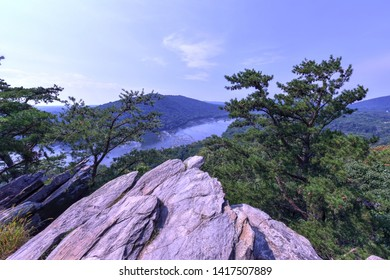 Panoramic view of the Potomac River atop Weverton Cliffs on the Appalachian Trail.   A rocky outcrop points toward the river below, surrounded by evergreens. Scenic mountaintop view on a summer day.