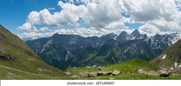 Panoramic view from Pramarnspitze saddle on snow-capped moutain panorama at Stubai hiking trail, Stubai Hohenweg, Alpine landscape of Tyrol Alps, Austria. Summer blue sky, white clouds