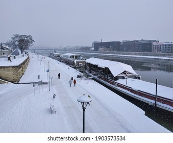 Panoramic view of promenade along Wisla (Vistula) River in Krakow, Poland covered in snow. People walking on white boulevard in freezing temperatures. Concept of Krakow in winter. - Shutterstock ID 1903573534