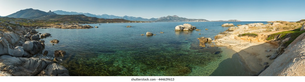 Panoramic view from Punta Spano at Sant' Ambroggio in Corsica across Calvi bay towards Calvi with shallow, turquoise water and rocks in the foreground and blue sky above
