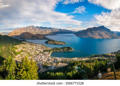 Panoramic View from Queenstown Skyline over the alpine city and Lake Wakatipu, with the Remarkable mountains in the background, at golden hour on a beautiful summer day.  New Zealand - South Island.