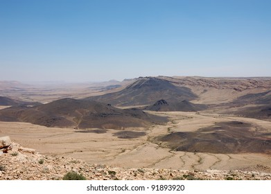 Panoramic view of Ramon crater with black lava heaps, Negev desert in Israel.