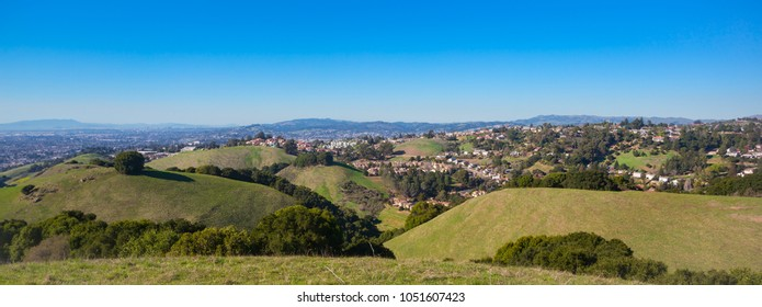 Panoramic view of residential homes on green rolling hills with blue sky