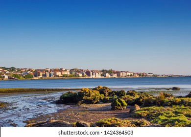 Panoramic view of Rianxo cityy seafront with coastal rocks at foreground, Galicia, Spain