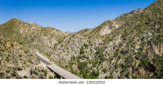 Panoramic view of rocky desert mountains above a desert road and bridge.
