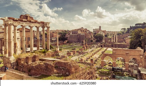 Panoramic view of the Roman Forum in summer, Rome, Italy. The Roman Forum is the remains of architecture of the Roman Empire. Vintage panorama of ancient ruins in Rome center on a sunny day.