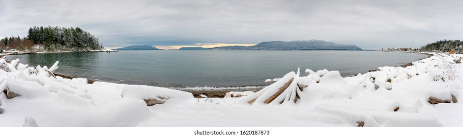 Panoramic View of Rosario Strait After a Winter Snowstorm. Seen from Lummi Island in the Pacific Northwest, Orcas Island in the background, receives a dusting of snow in the Salish Sea.