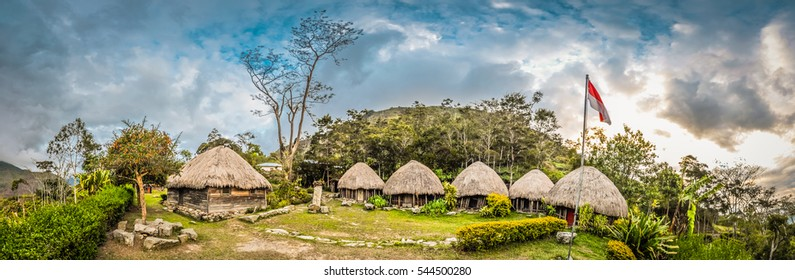 Panoramic view of row of traditional houses with straw roofs in village with flag in Dani circuit near Wamena, Papua, Indonesia.