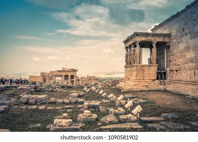 Panoramic view of ruins on the Acropolis of Athens, Greece. Erechtheion temple with Caryatid Porch in the foreground. Ancient Greek buildings at the top of Acropolis hill. Main landmark of Athens.