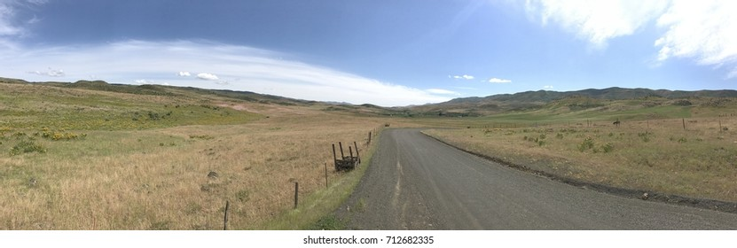 Panoramic view of rural dirt road winding through the valley