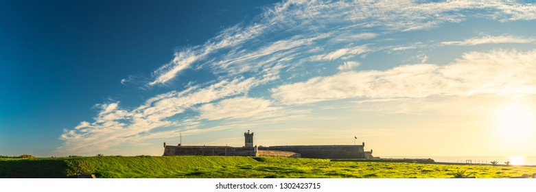 Panoramic view of Saint Julian Fortress lighthouse tower standing behind empty land with green grass Oeiras, Lisbon