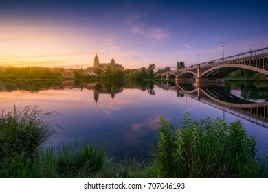 Panoramic view of Salamanca reflected in the river Tormes during sunset, Spain.
