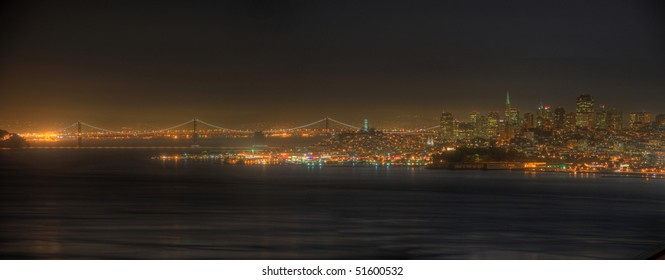 A panoramic view of the San Francisco skyline and the San Francisco Bay Bridge at night.