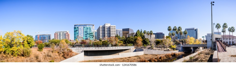 Panoramic view of San Jose's downtown skyline as seen from the shoreline of Guadalupe river on a sunny fall day; Silicon Valley, California