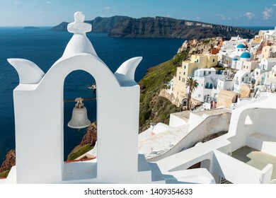 panoramic view of the Santorini caldera and Oia, with a church bell tower in foreground and iconic blue church domes in the background