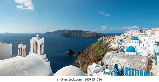 panoramic view of the Santorini caldera and Oia, with a church bell tower and iconic blue church domes