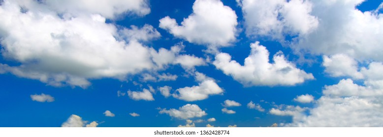 Panoramic view of scattered clouds against a bright blue sky