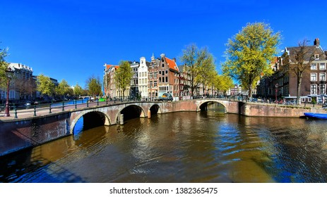 Panoramic view of the scenic canals of Amsterdam with traditional houses and bridges, Netherlands