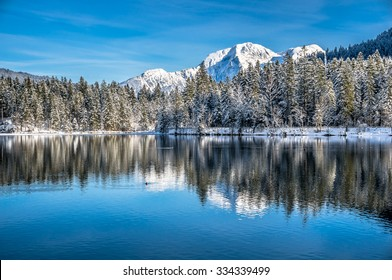 Panoramic view of scenic idyllic winter landscape in the Bavarian Alps at famous mountain lake Hintersee, Ramsau, Nationalpark Berchtesgadener Land, Upper Bavaria, Germany