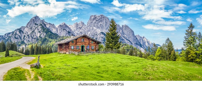 Panoramic view of scenic mountain landscape in the Alps with traditional old mountain chalet and fresh green meadows in springtime